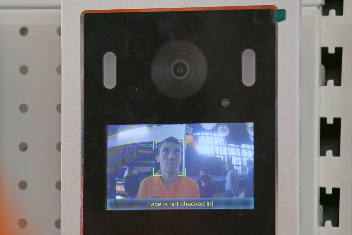 """A facial recognition-based check-in system on display at an integrated security exhibition in Yalta, Crimea. It shows a camera and an attached screen that displays a man's face. A green box outlines and detects the man's face on the screen. The text on the screen reads, """"Face is not checked in!"""""""