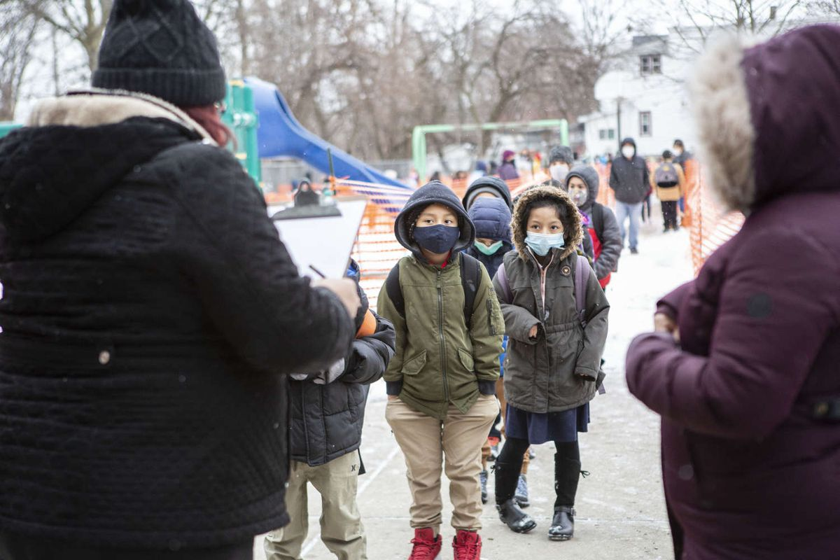 Students line up to enter school wearing masks