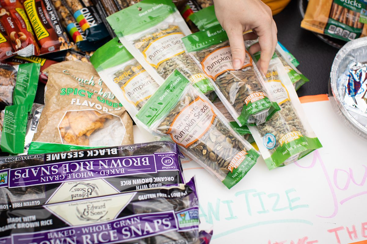A hand holds a container of pumpkin seeds, which rests on a table next to rice crackers, granola bars, and other snacks