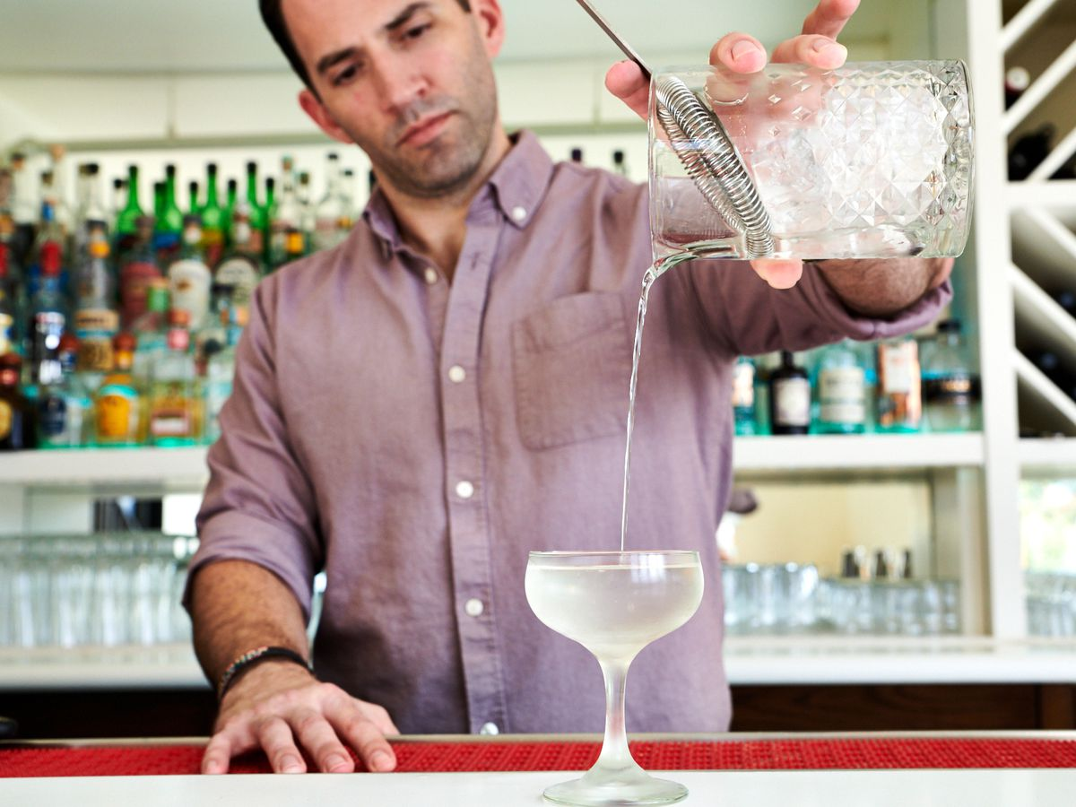 Ricky Gomez pours a martini into a coupe glass behind the white-and-turquoise bar at Palomar