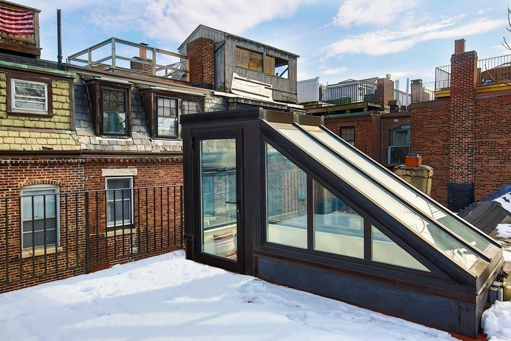 A glass head house at the top of some stairs, leading to a roof deck.