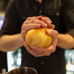 To start, Hammett peels a grapefruit and adds two peels to a cocktail tumbler. Grapefruit, rather than lemon or orange, pairs better with the herbs he adds later. Hammett adds that grapefruit, rather than oranges, as they are easier to source locally in T