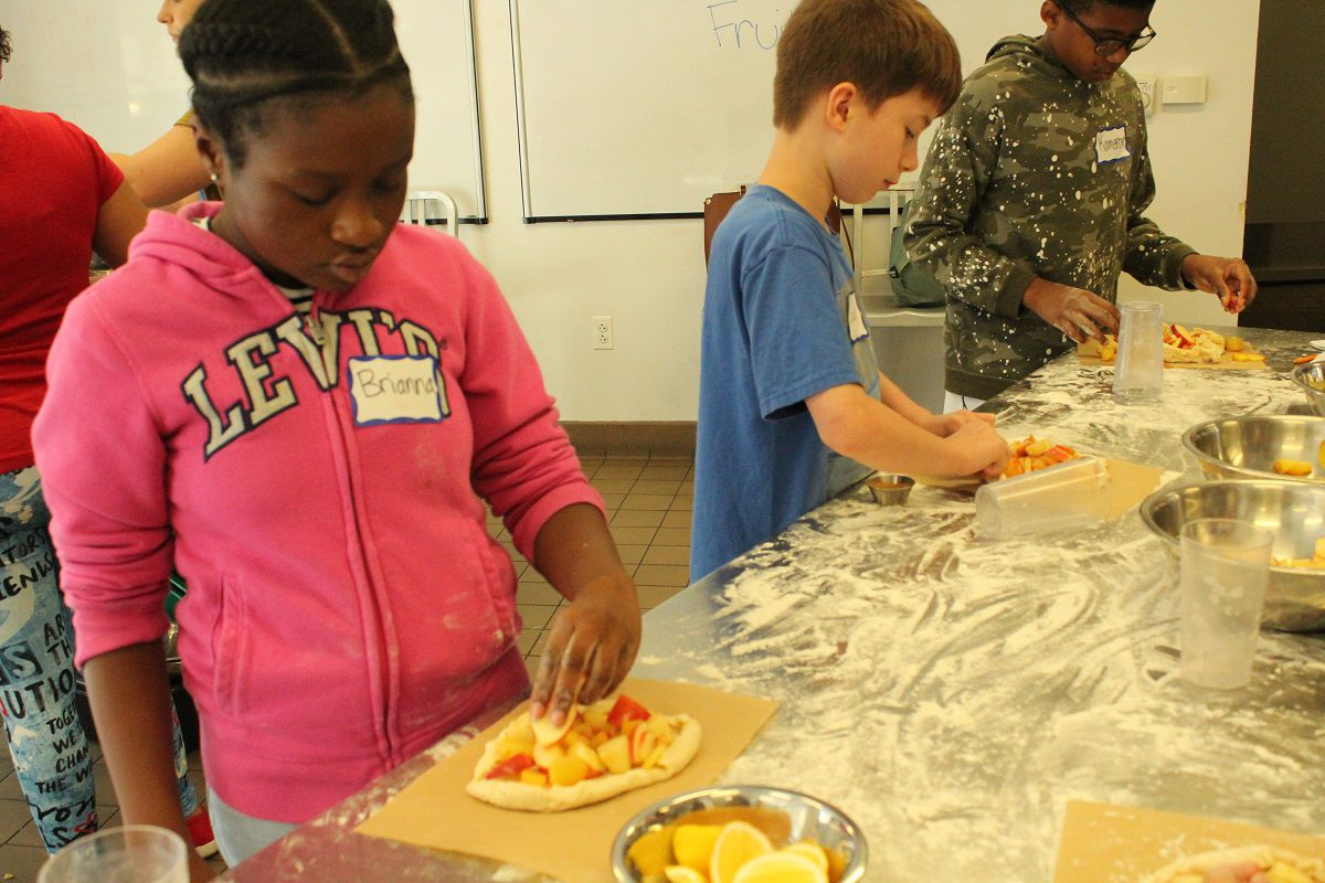 Brianna Burrell, 10, learns how to make a galette, or fruit pie, at Parkway Central Library.