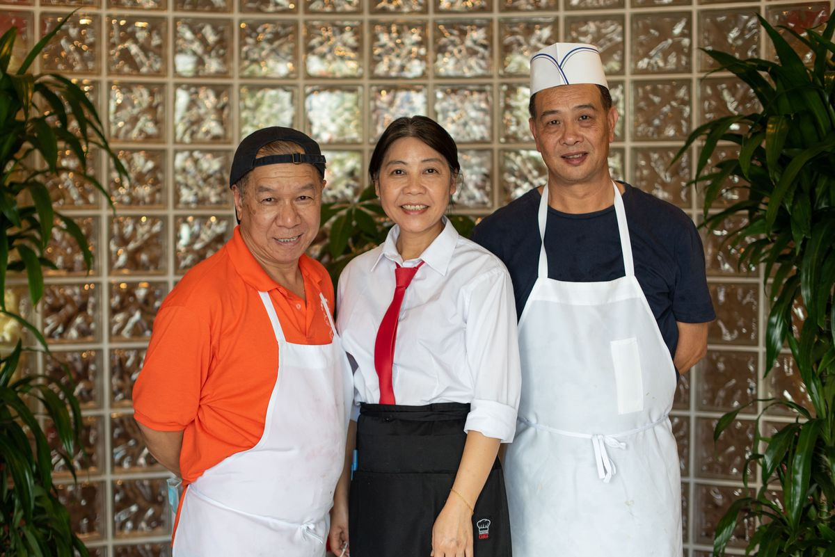 A portrait of three restaurant owners. Two men and a woman. The men wear kitchen aprons while the woman wears a red tie against a white shirt.