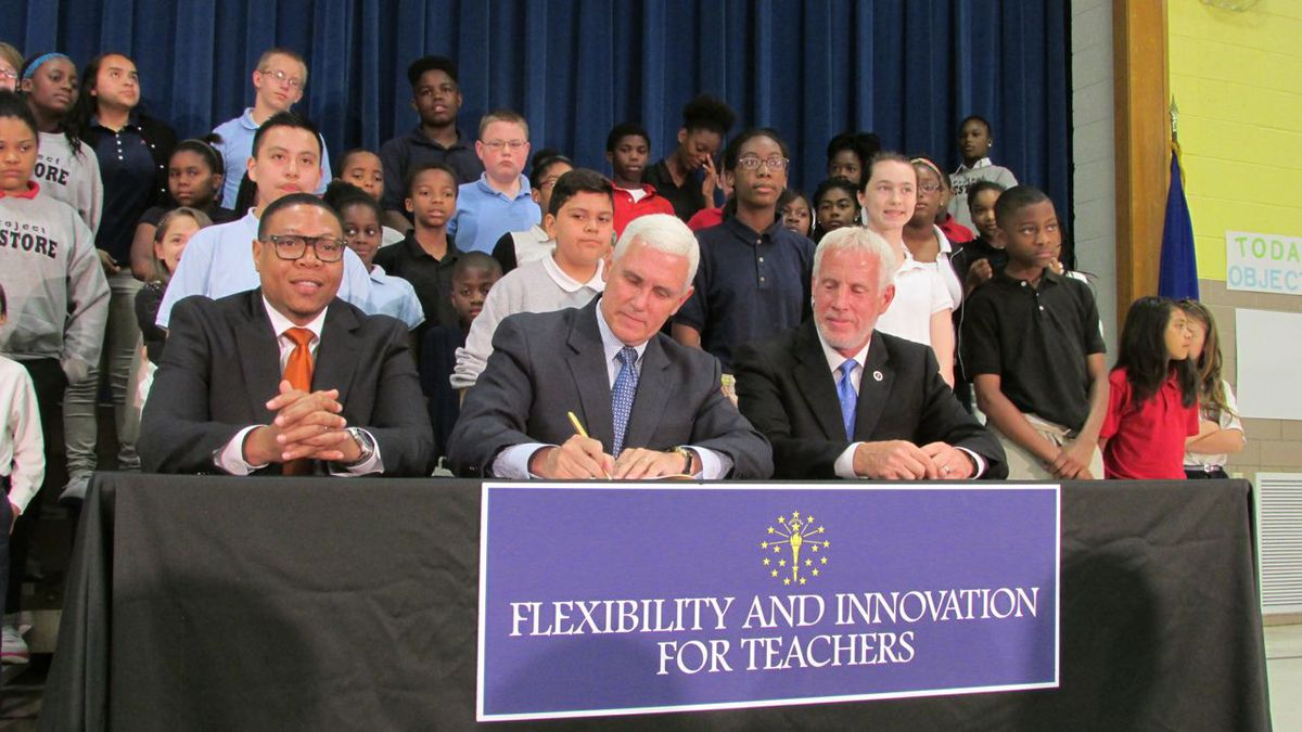 Pence signs House Bill 1009 while IPS Superintendent Lewis Ferebee (left) and Indiana House Education Committee Chairman Robert Behning, R-Indianapolis, and School 88 students look on.