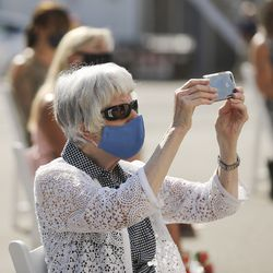 """Pamela Atkinson takes a photo of the """"Utah Women 2020"""" mural on the Dinwoodey Building in Salt Lake City during its unveiling on Wednesday, Aug. 26, 2020. The mural, commissioned by Zions Bank in honor of women's suffrage, depicts images of 250 Utah women past and present, including Atkinson."""
