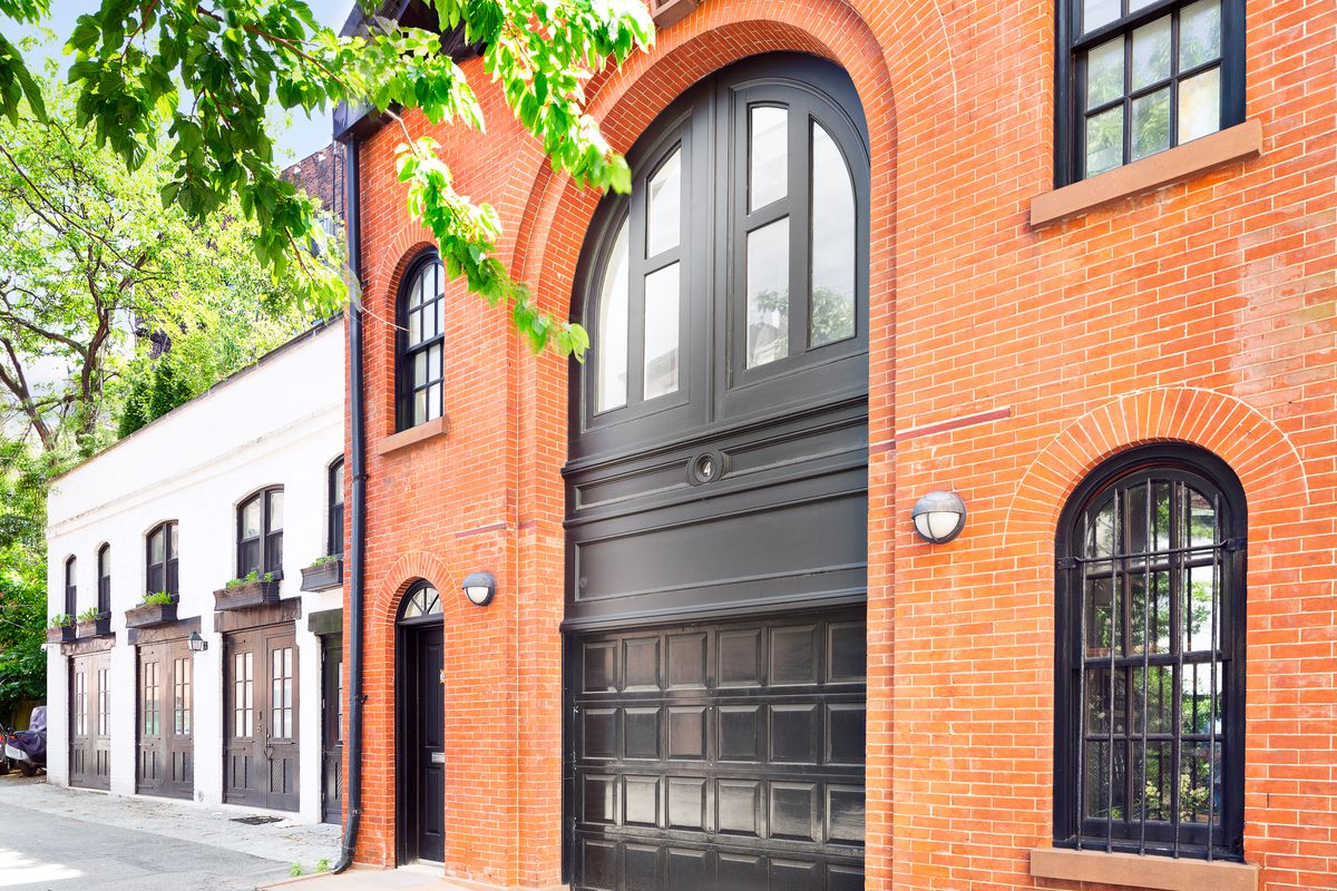 The entrance to a two-story brick carriage house.