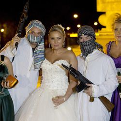 In this Sunday, Aug. 26, 2012 picture, a Romanian bride poses with mock kidnappers holding a toy weapons at the Triumph Arch in Bucharest, Romania. The arch, a replica of the Arc de Triomphe in Paris, the French capital, is a rendezvous place for brides on the wedding night for the bride stealing ritual. The ancient Romanian tradition of bride stealing is getting bigger, brasher and an increasingly common sight in the Romanian capital, the region's undisputed party town.