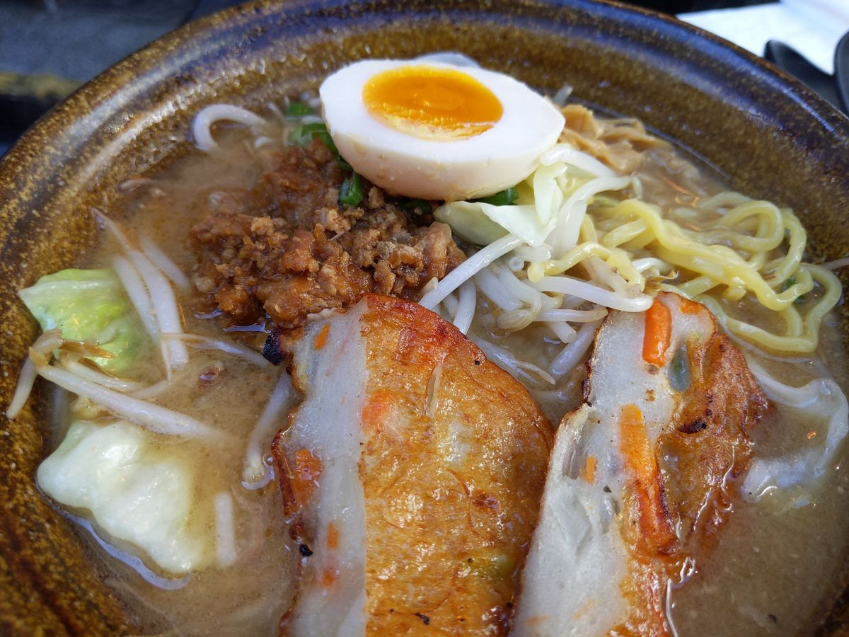 A bowl of ramen with boiled egg, fish caked, and napa cabbage sticking out of a beige broth.