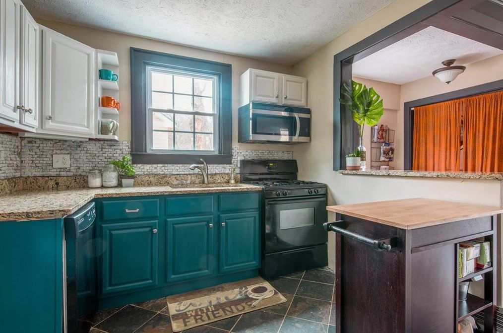 A bright blue kitchen with brown granite countertops.