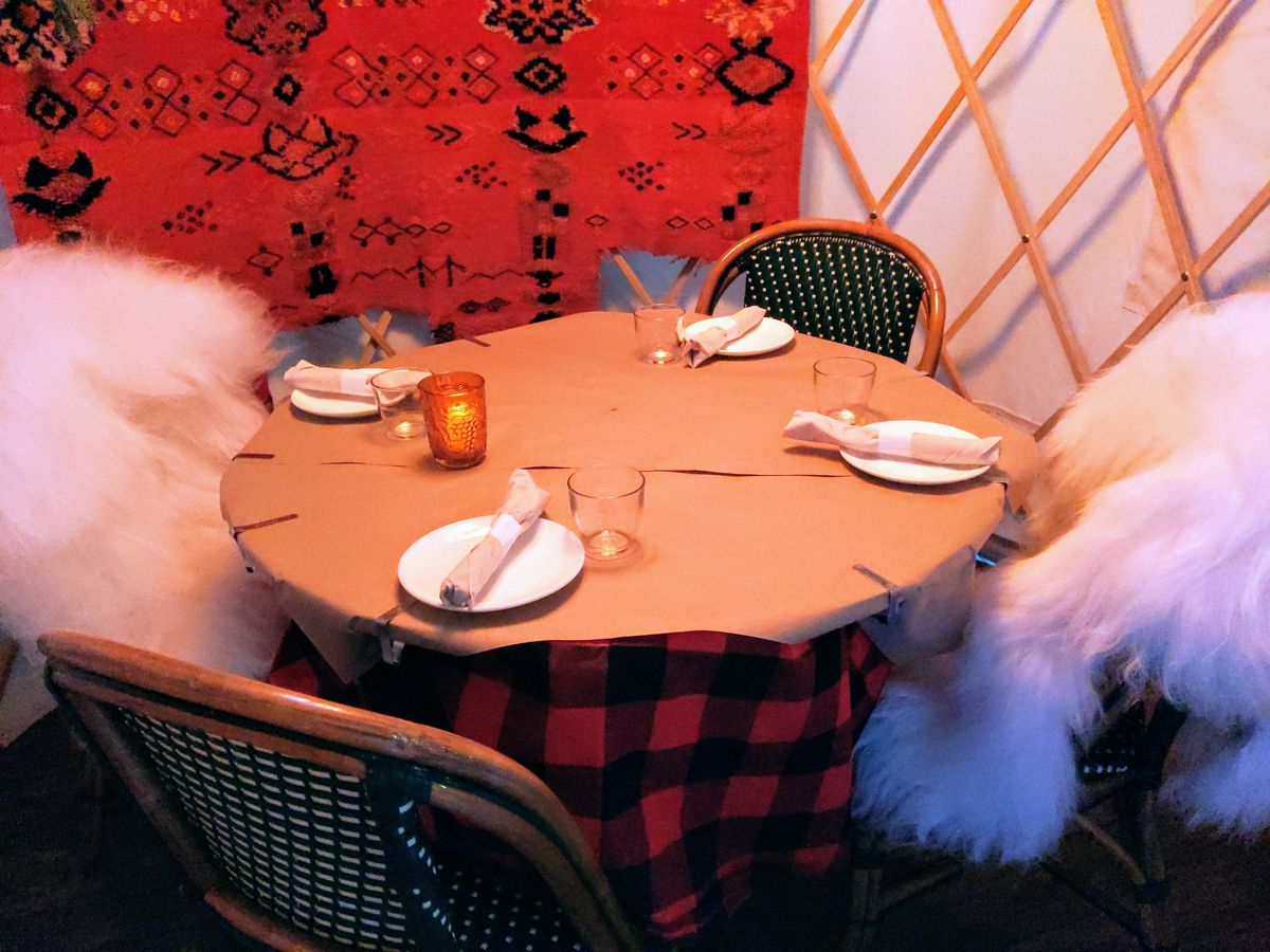 The inside of a yurt with sheepskins draped over chairs.