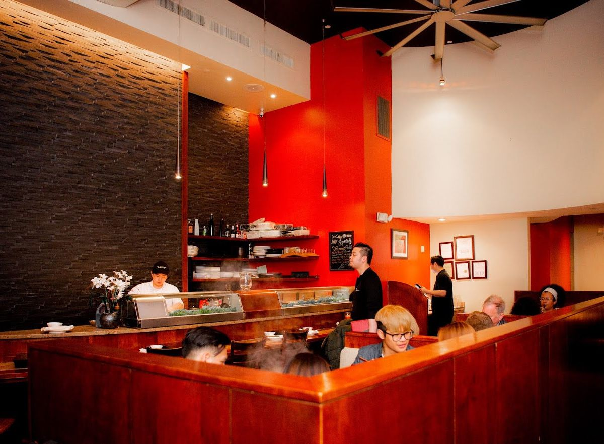A restaurant interior full of diners. The space features brick and bright red accents.