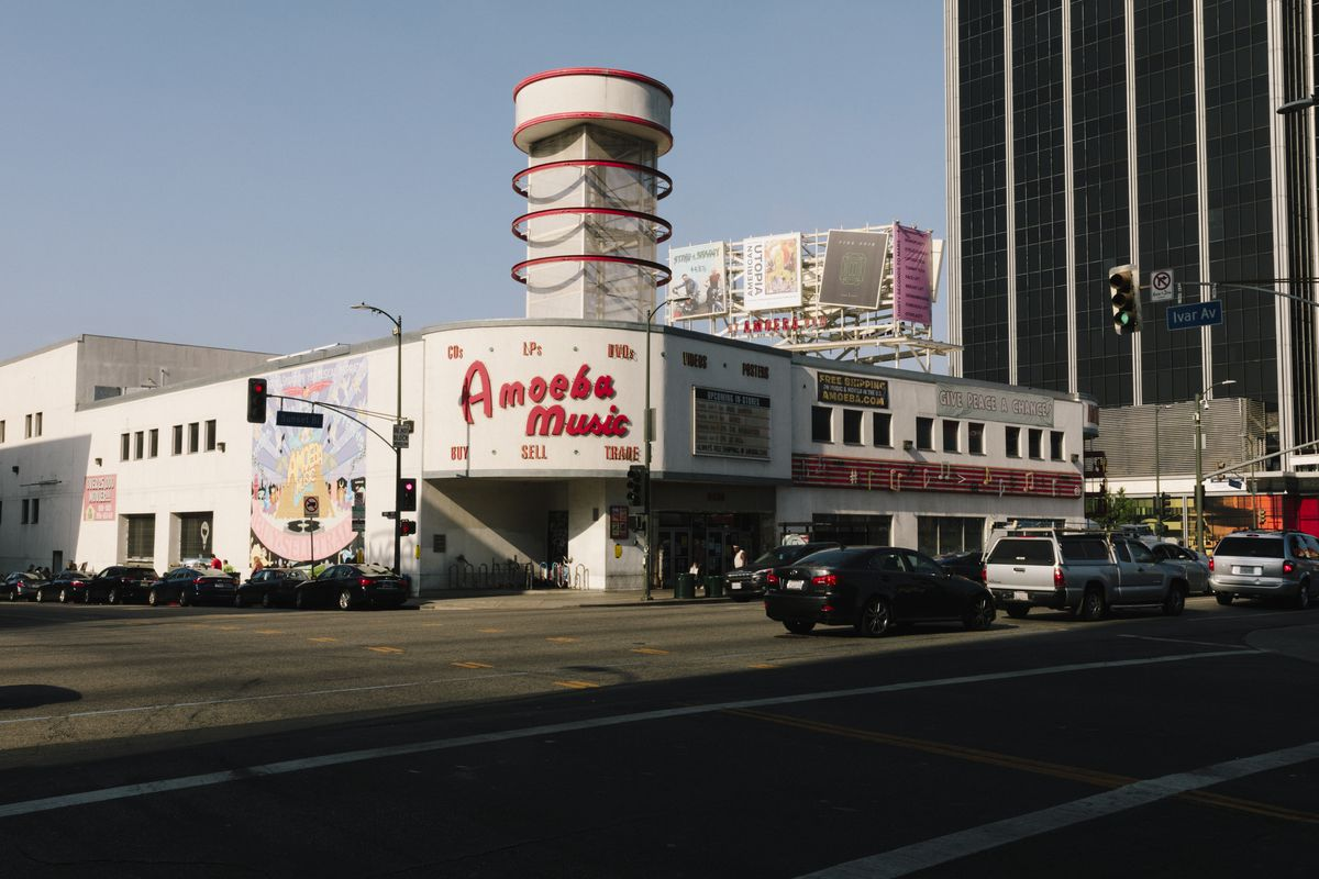 """A photo of a low-rise, white, stucco building with exterior murals and neon signs, including one that says """"Amoeba Records"""" in red letters on the front."""