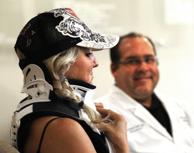 Bull riderMaggie Parkerwears a protective brace as she talks with neurosurgeon Richard Teff at St. Vincent Healthcare in Montana.