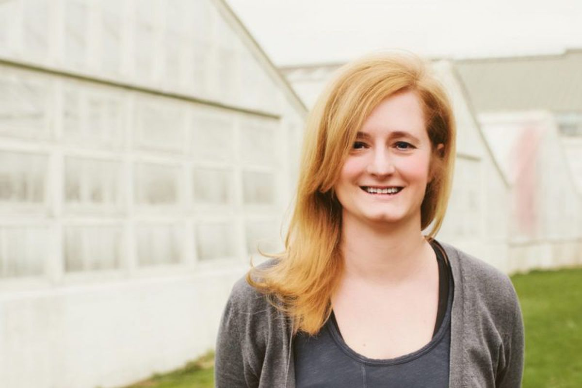 A white woman with strawberry blonde hair stands in front of a translucent greenhouse.