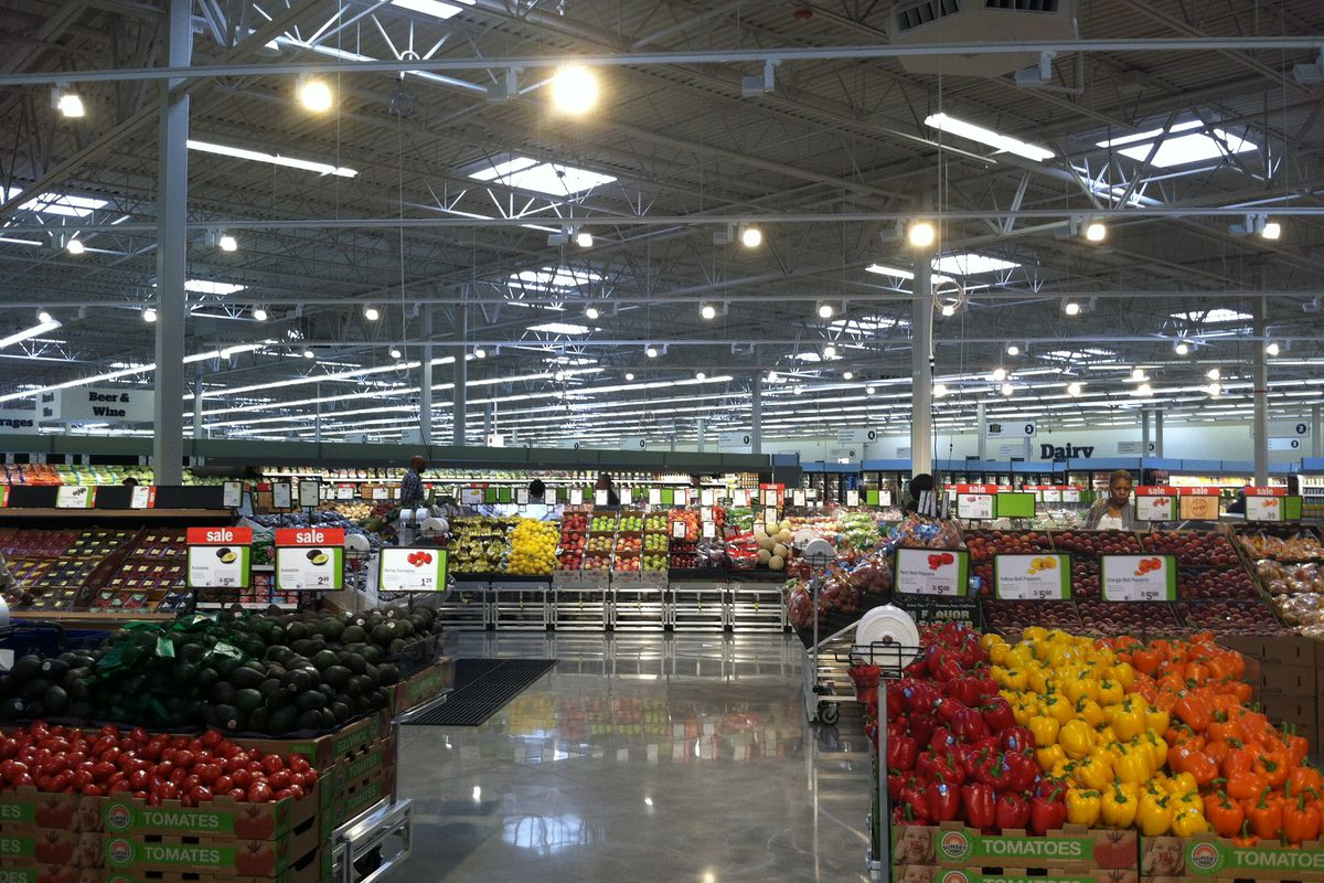 A grocery aisle filled with fruits and vegetables.