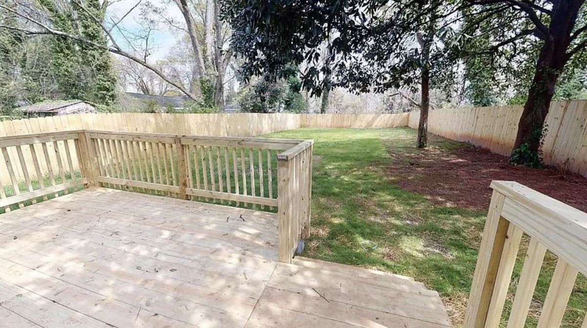 View of fenced backyard from deck.