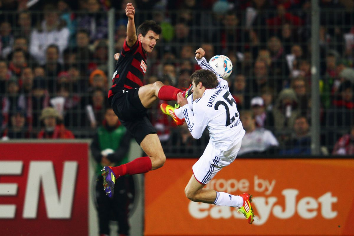 Thomas Mueller (R) of Muenchen is challenged by Ivan Santini of Freiburg during the Bundesliga match between SC Freiburg and FC Bayern Muenchen at Mage Solar Stadium on February 18, 2012 in Freiburg im Breisgau, Germany.