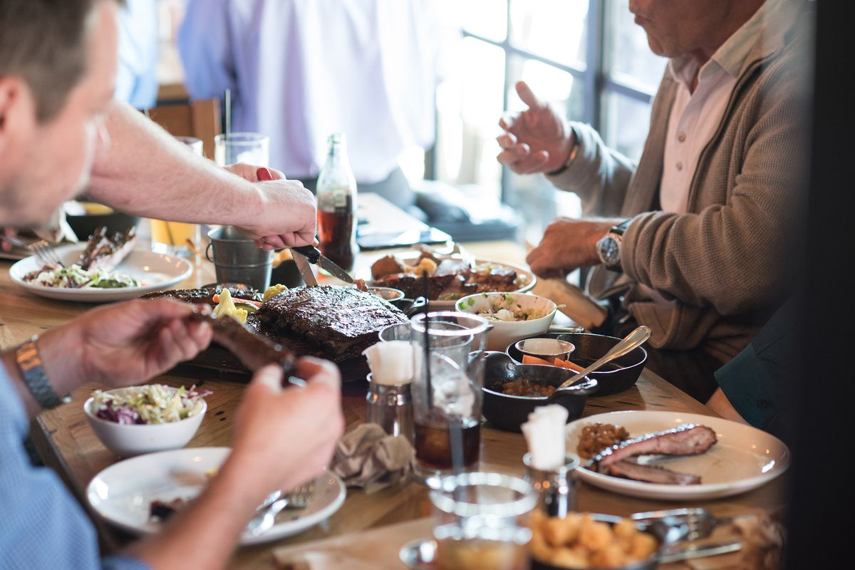 A server asks for information from diners at a barbecue restaurant.