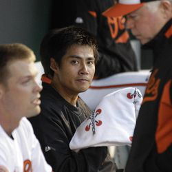 Baltimore Orioles starting pitcher Wei-Yin Chen, of Taiwan, center, looks on as catcher Matt Wieters, left, speaks with manager Buck Showalter in the dugout in the first inning of a baseball game against the New York Yankees in Baltimore, Tuesday, April 10, 2012.