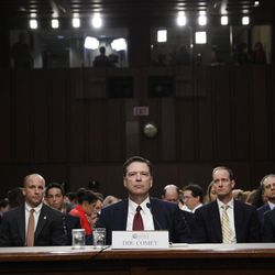 Former FBI director James Comey listens to the committee chairman at the beginning of the Senate Intelligence Committee hearing on Capitol Hill, Thursday, June 8, 2017, in Washington.