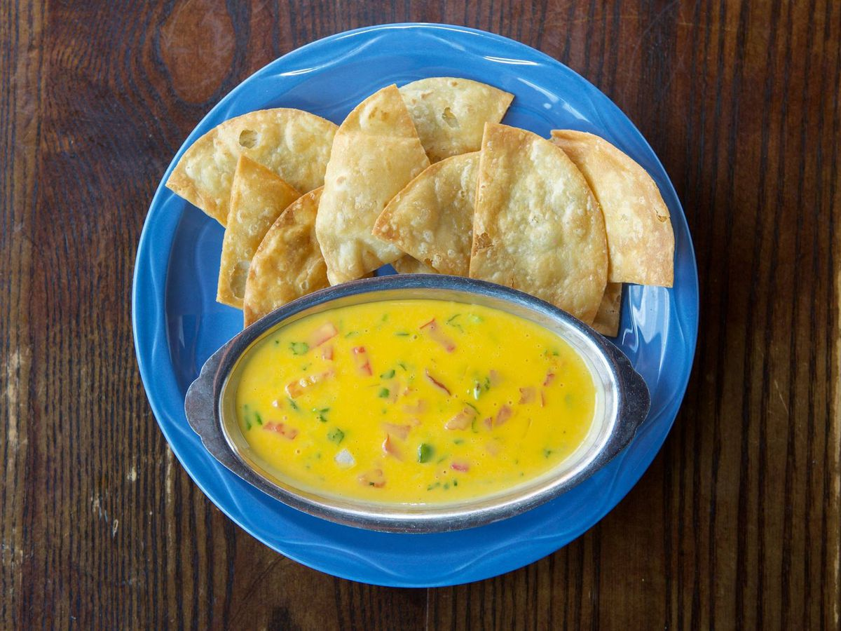 overhead view of a large bowl of queso and a pile of tortilla chips on a bright blue plate.