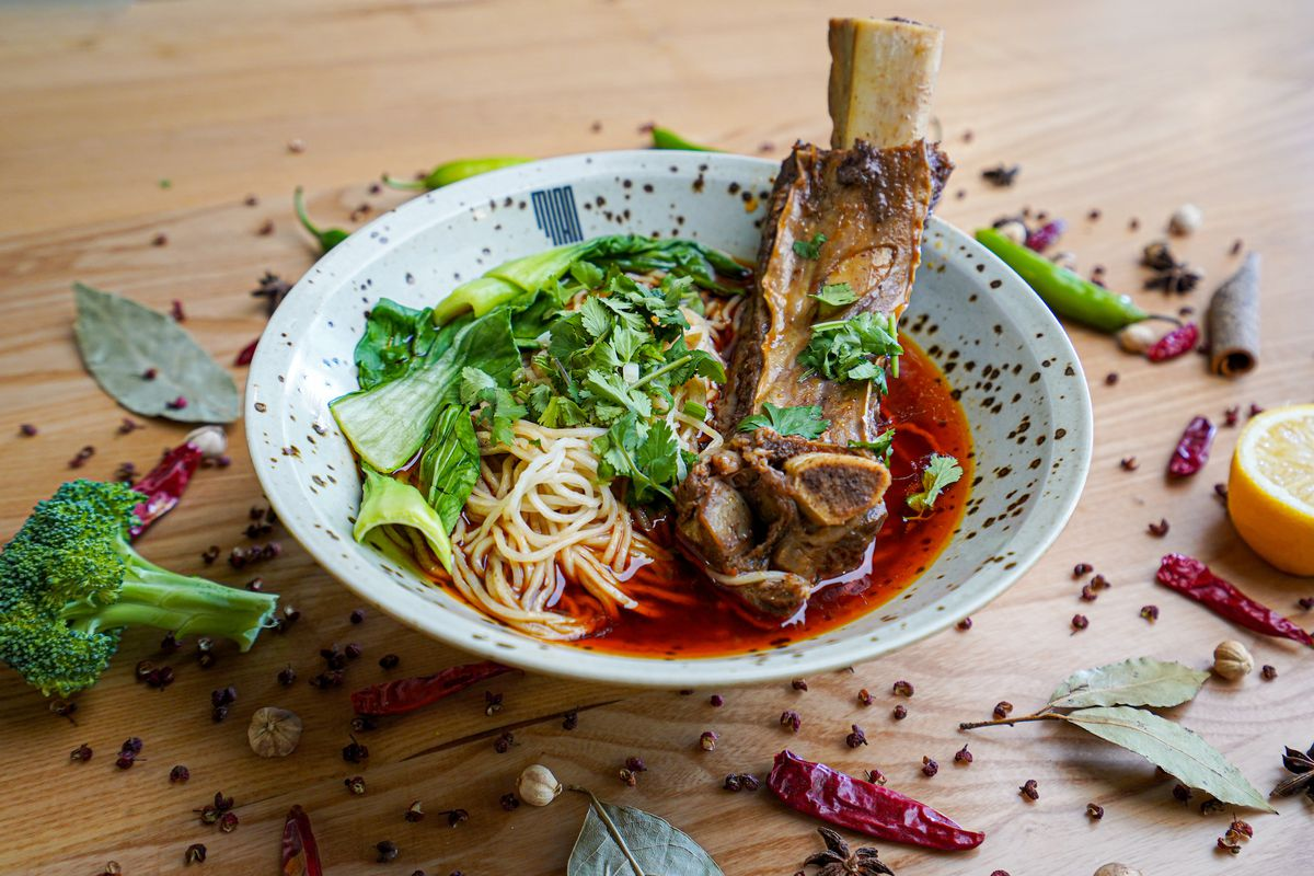 A splattered bowl containing noodles, thin red sauce, and a beef rib.