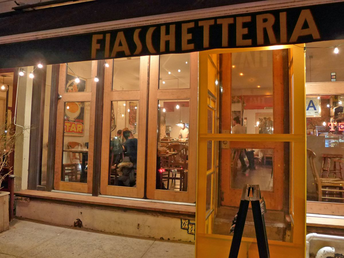 The exterior of Fiaschetteria Pistoia, with floor to ceiling window panels that give a view into the restaurant