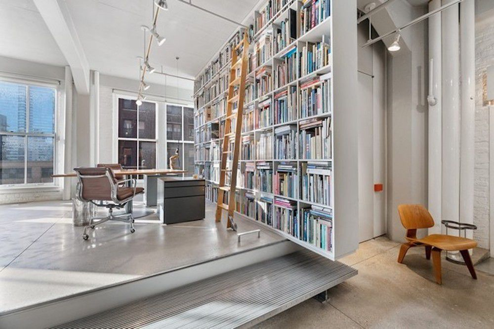 Two steps up lead toa sitting area with a desk next to a large white bookshelf and a wall of windows.