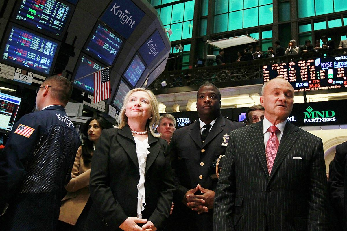 Then-Secretary of State Hillary Clinton (C), and then-New York City Police Commissioner Ray Kelly (L) walk on the floor of the New York Stock Exchange after the ringing of the opening bell on September 9, 2011, in New York City.