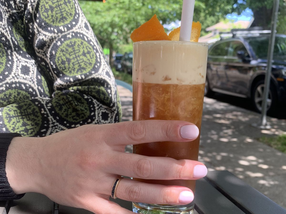 A woman's hand with pink fingernails holds a Collins glass on a dark wooden table. The drink is dark brown with a layer of white foam.