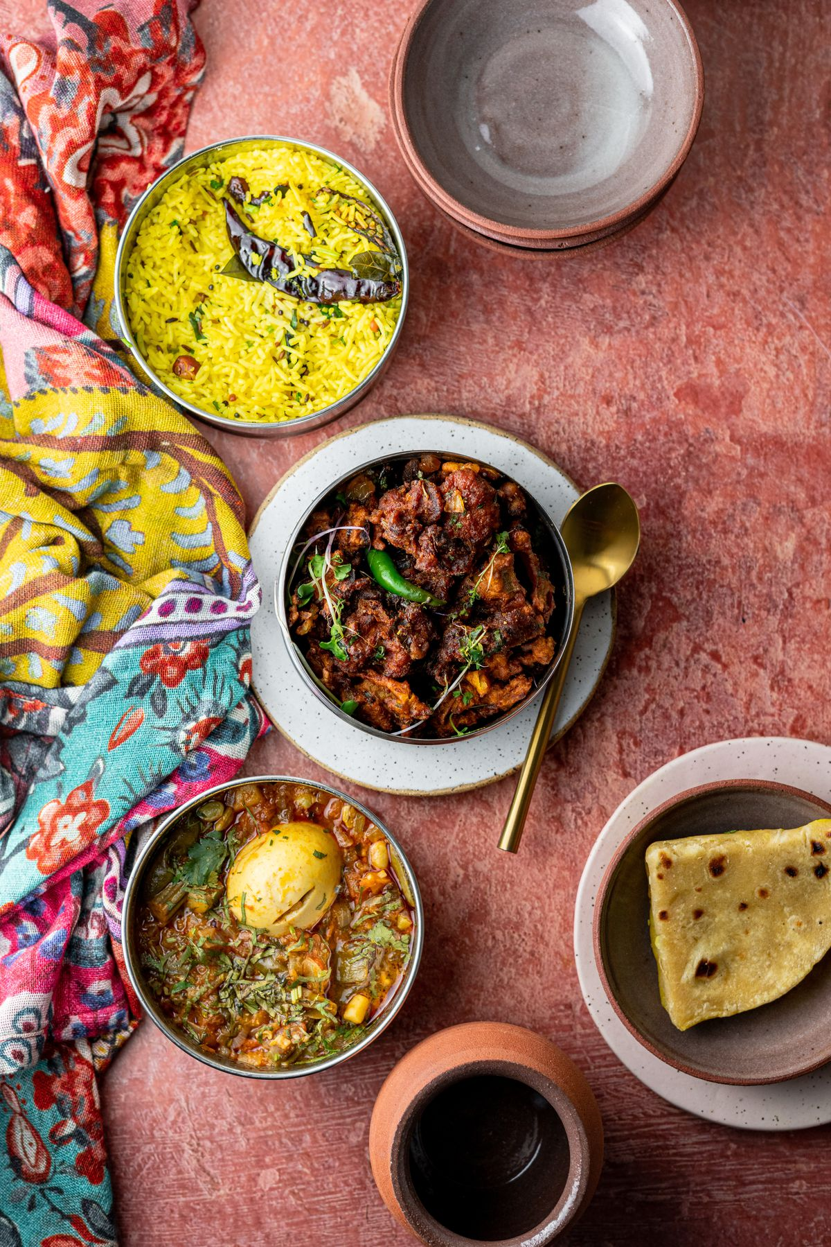 Four indian food dishes placed on a red background