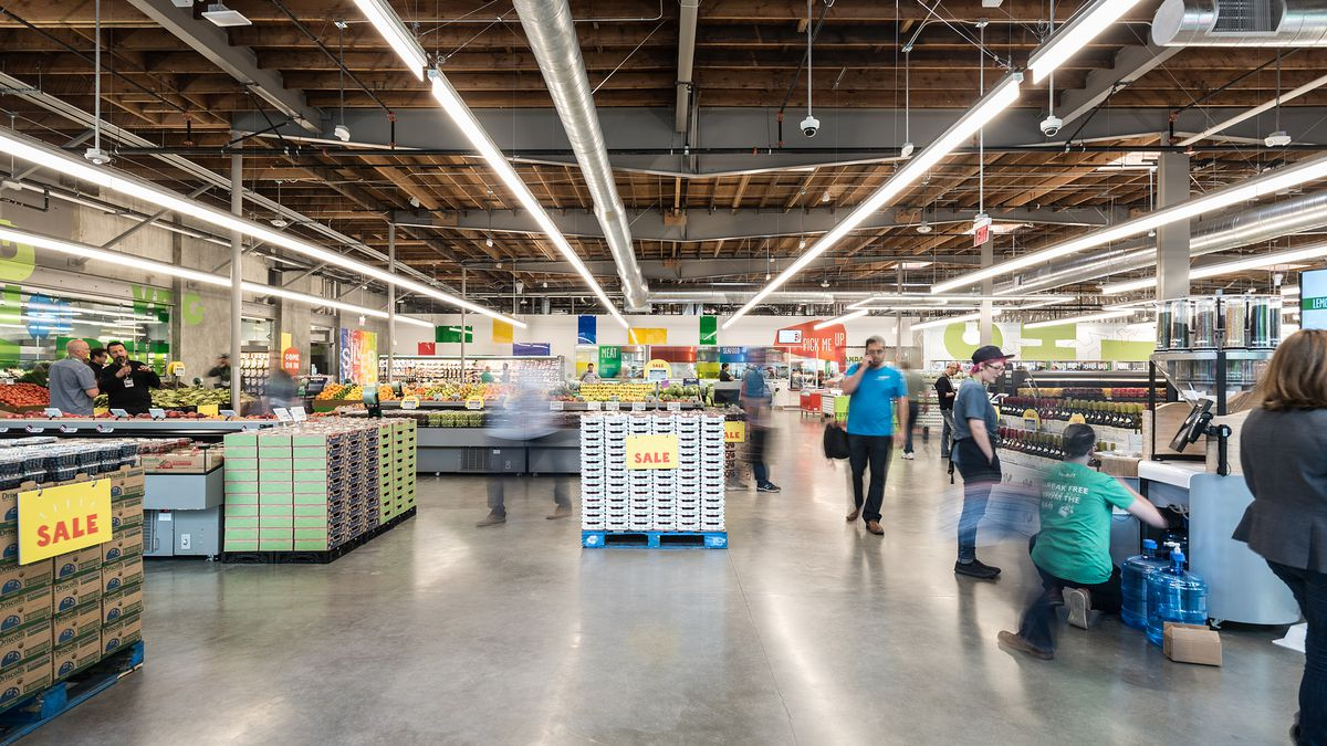 A well-lit grocery store with just a few people inside.