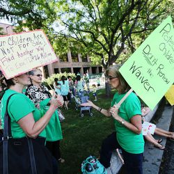 Charlotte Wakefield, Anne Marie Oborn and Kris Kimball talk as they join other protesters demonstrating Friday, Aug. 8, 2014, prior to the Utah Board of Education's vote on whether to request an extended waiver from the Adequate Yearly Progress requirements of No Child Left Behind.