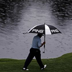 Angel Cabrera, of Argentina, walks down the 16th fairway in the rain during the first round of the Masters golf tournament Thursday, April 5, 2012, in Augusta, Ga.