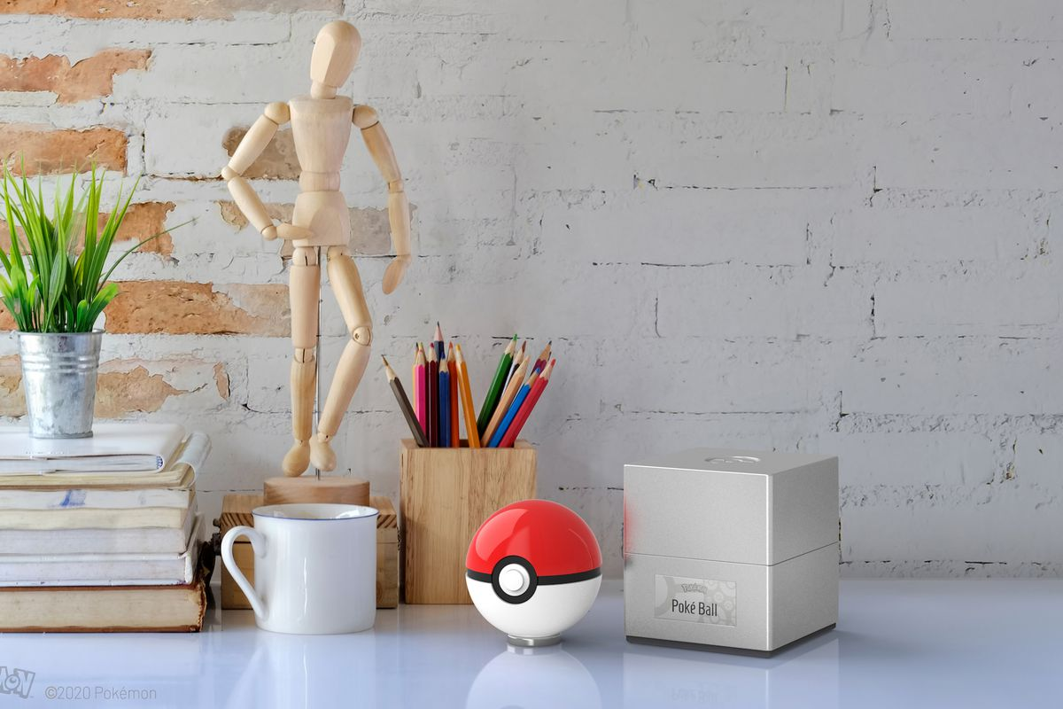 A photo of a white desktop with a Poké Ball replica, its case, a mug, and other items
