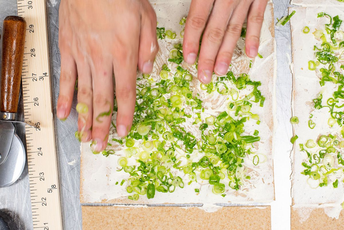 Two hands are shown from above pressing scallions into dough. On the left is a dough cutter and a ruler.