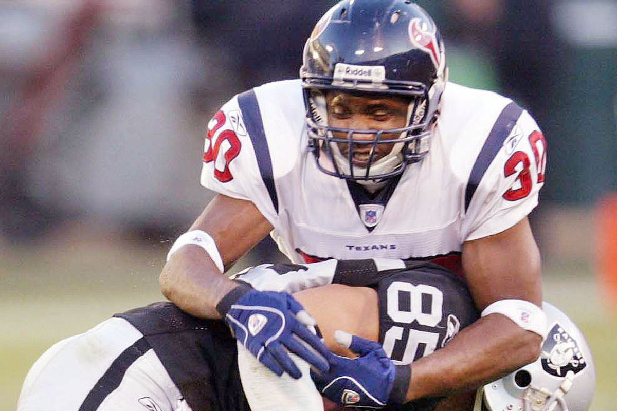 Raiders' John Madsen is wrapped up by Houston's Jason Simmons during a game against the Houston Texans at McAfee Coliseum on Sunday, Dec. 4, 2006, in Oakland, Calif. (Jane Tyska/The Oakland Tribune)
