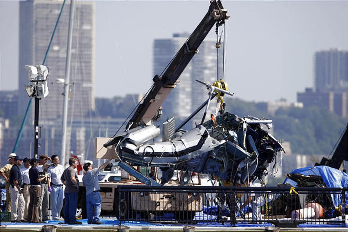 The wreckage of a helicopter that was hit by an airplane and crashed in the Hudson River is repositioned by a crane on a pier in Hoboken, NJ.