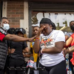 Zahrya Grimes, niece of Verndell Smith, is comforted by family and friends while she speaks to reporters at Ultimate Threat Dance Organization's studio, Thursday, May 20, 2021. Verndell, the founder of the dance studio was shot and killed yesterday.