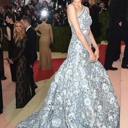"""Allison Williams wears a Peter Pilotto gown, Soraya Silchenstedt x La Ligne earrings, and an Edie Parker x La Ligne clutch that says, """"Read Between the Lines"""" and """"Color Outside the Lines""""."""
