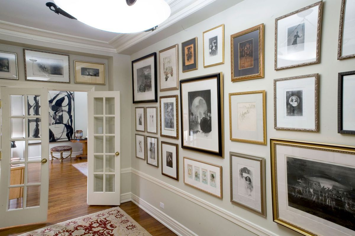 A wall covered in framed photos and artworks.