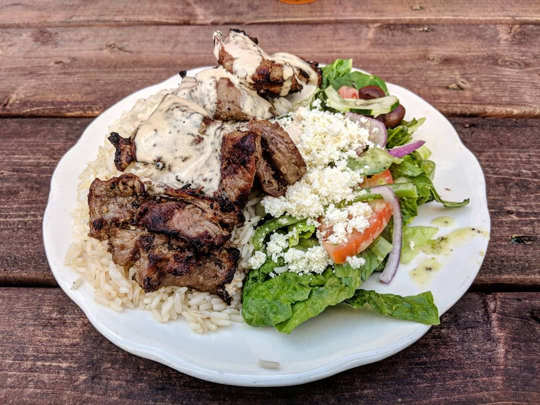 Lamb, rice, and salad sit on a white plate on a picnic table
