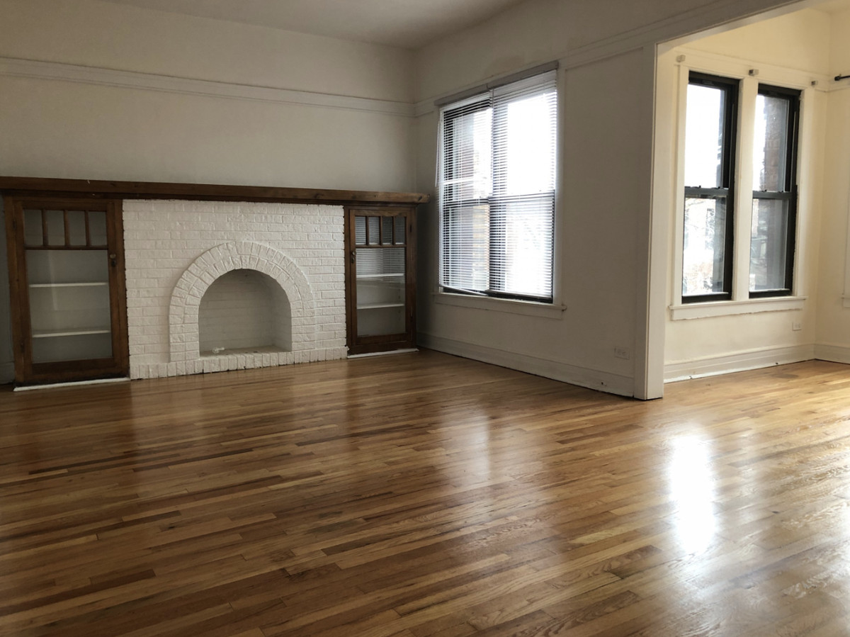 A living room with a side sunroom. There is a brick fireplace and two shelves framing it.