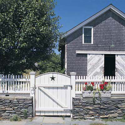 A combination of a stone wall and a white fence.