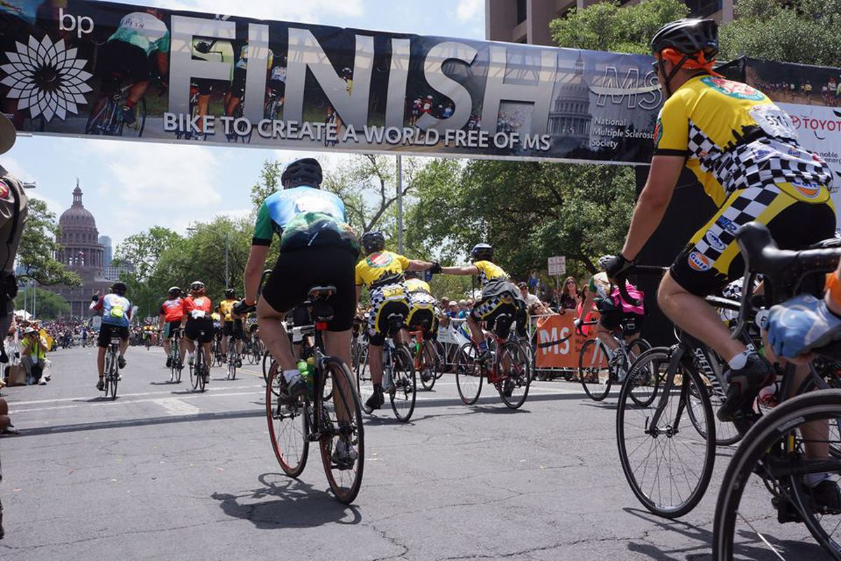 Bicyclists riding under a Finish Line banner toward Texas state Capitol
