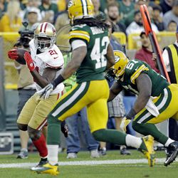 San Francisco 49ers' Frank Gore (21) breaks away from Green Bay Packers' Morgan Burnett (42) and  D.J. Smith (51) for a touchdown run during the second half of an NFL football game Sunday, Sept. 9, 2012, in Green Bay, Wis. The 49ers won 30-22.