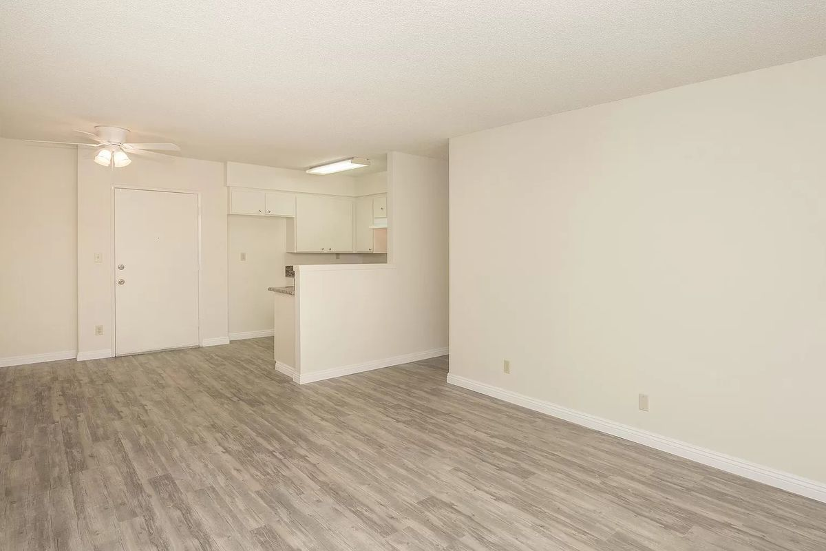 A living room with gray laminate floor and white walls