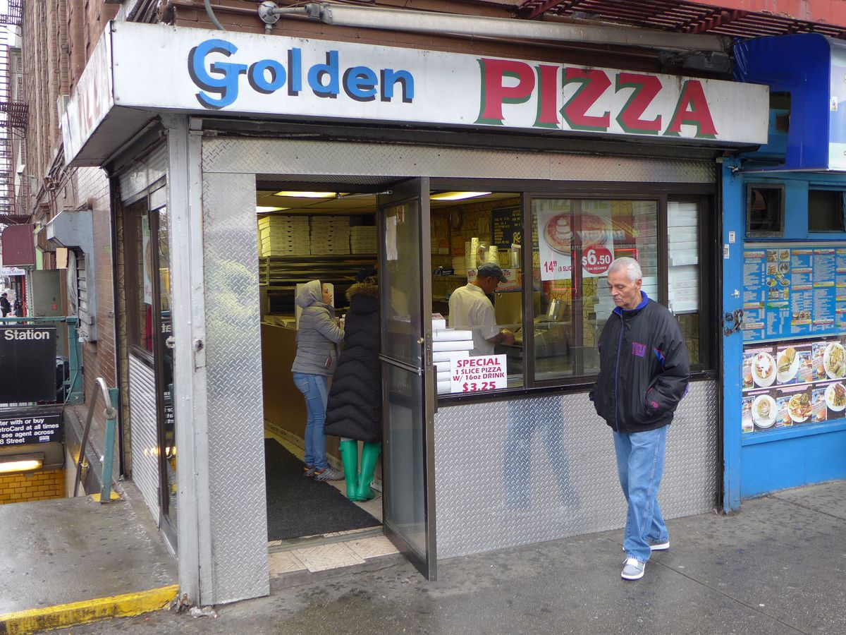 A very plain storefront on a corner with a gray haired man standing in front.