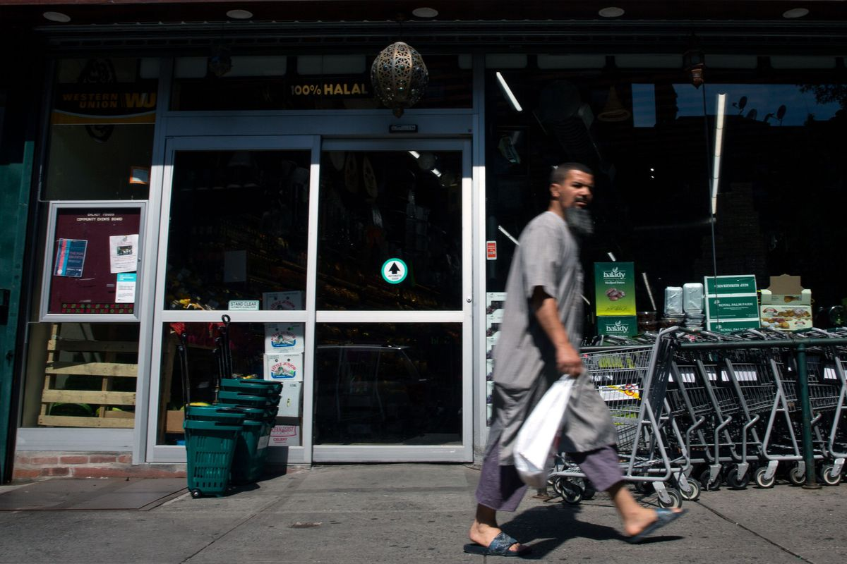 A man walks past a halal grocer on Fifth Avenue and 72nd Street in Bay Ridge, Brooklyn, on July 14, 2019.